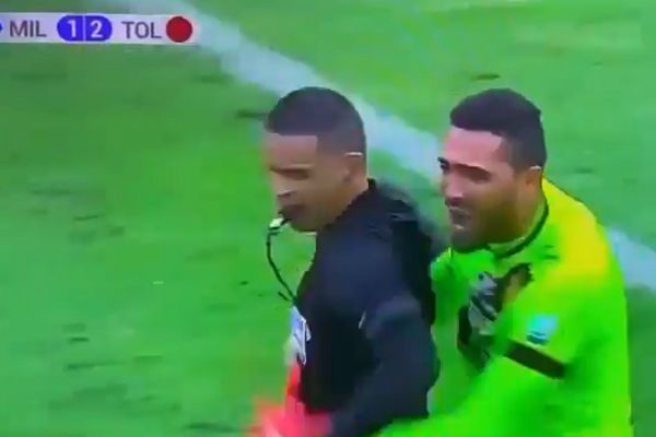 Deportes Tolima goalkeeper Álvaro Montero hugs referee after final whistle of win at Millonarios