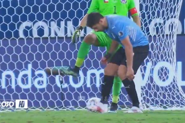 Uruguay's Luis Suárez fixes boot in front of Chile goalkeeper Claudio Bravo
