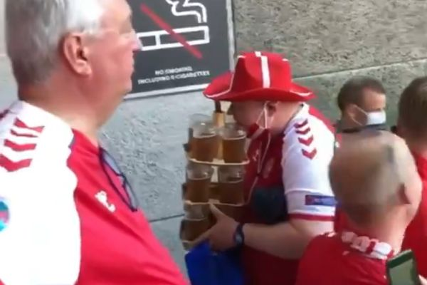 Danish supporter carries a dozen beers and a hotdog at Euro 2020 win over Russia